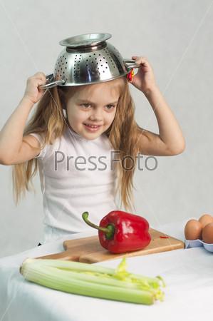 Девочка играет в повара в дуршлаге на голове