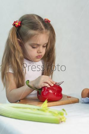 Девочка режет красный перец ножом, играя в повара
