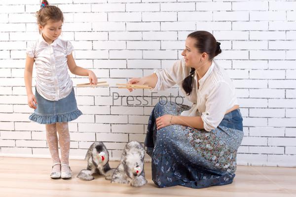 Мать и дочь играют с двумя игрушечными собаками