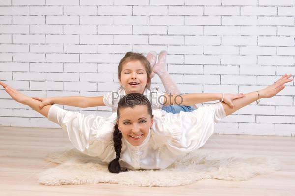 Дочь верхом на матери изображает полет