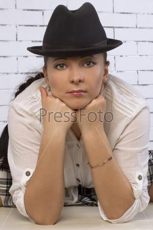 Женщина в шляпе, опирается подбородком на руки