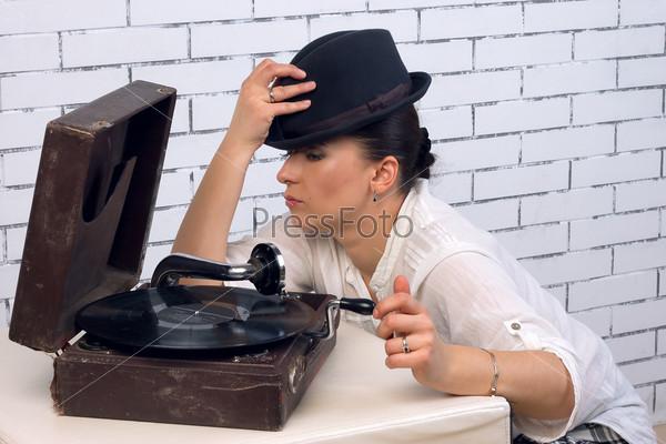 Фотография на тему Женщина в шляпе в пол-оборота у патефона