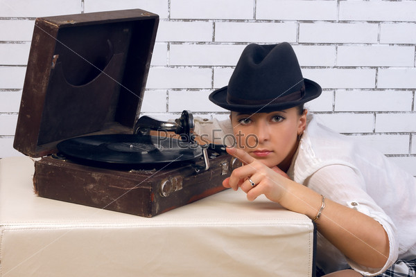 Женщина в шляпе в пол-оборота у патефона