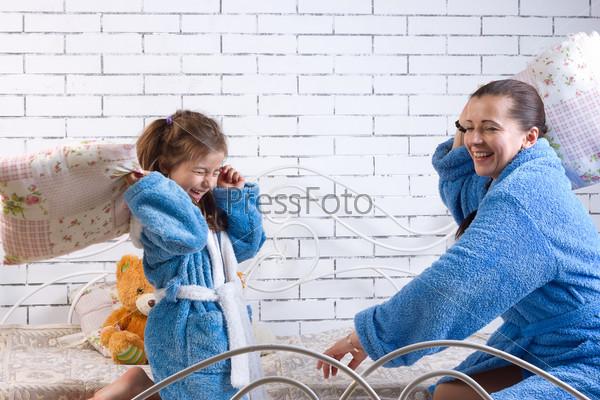 Мать и дочь в махровых халатах дерутся подушками