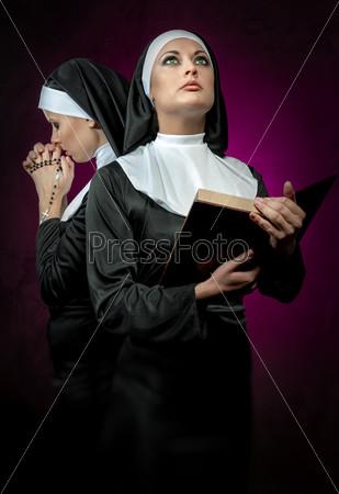 Две привлекательные молодые монахини с четками и Библией