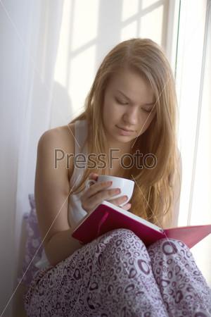 Фотография на тему Девушка с чашечкой читает книгу на подоконнике