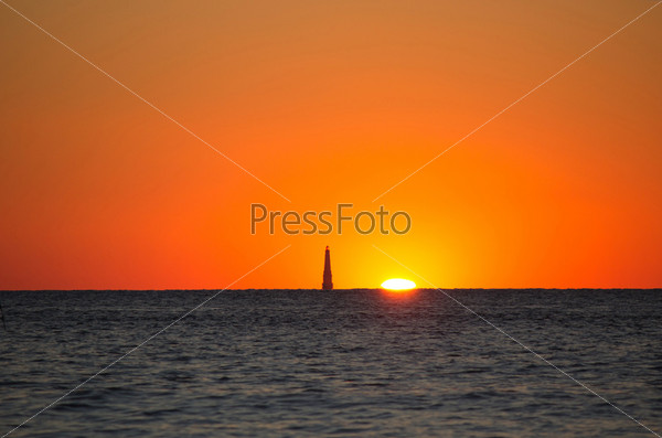 Маяк в море на закате