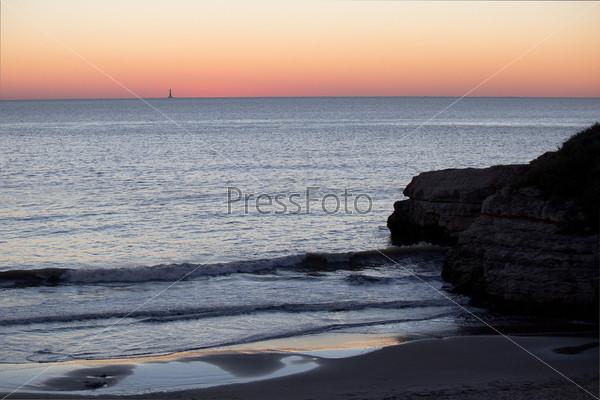 Маяк далеко в море и скалы на переднем плане