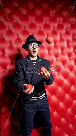 Мужчина-клоун жонглирует мячами