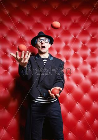 Фотография на тему Мужчина-клоун жонглирует мячами