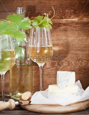 Бокалы белого вина, бутылка и сыр