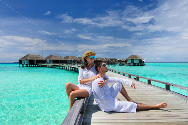 Пара на пляжном пирсе на Мальдивах