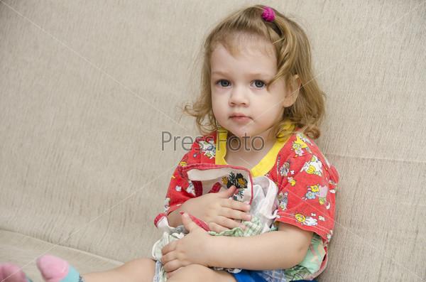Фотография на тему Маленькая девочка сидит на диване с платками в руках