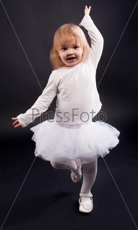 Двухлетняя девочка танцует в белом