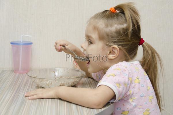 Девочка ест кашу за столом. Вид в профиль