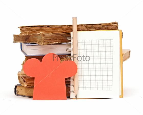 Поварской колпак, карандаш, блокнот и стопка книг на белом фоне