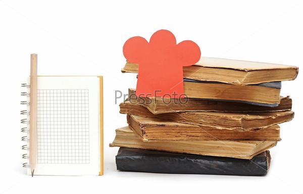 Фотография на тему Поварской колпак, карандаш, блокнот и стопка книг на белом фоне