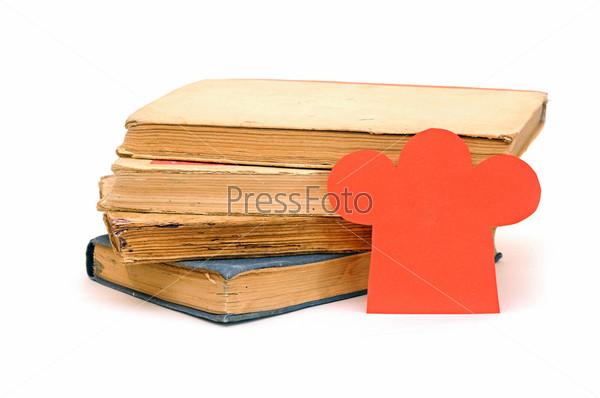 Стопка книг и бумажный поварской колпак
