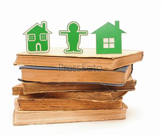 Маленький дом, человек и автомобиль на стопке книг