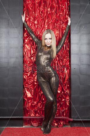 Красивая девушка стоит у красной стены