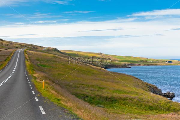Шоссе через исландский пейзаж под голубым небом