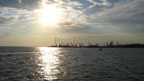 Вечернее море с подъемными кранами в порту