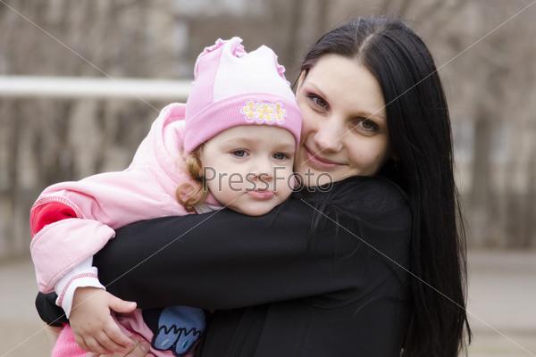 Фотография на тему Маленькая девочка задумчиво лежит на плече у мамы