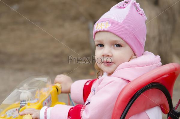 Фотография на тему Маленькая девочка смотрит в кадр сидя на велосипеде