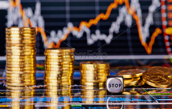 Кубик со словом STOP, стопки золотых монет и финансовая диаграмма как фон