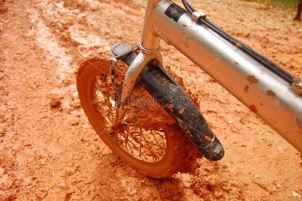 Коричневое грязное велосипедное переднее колесо
