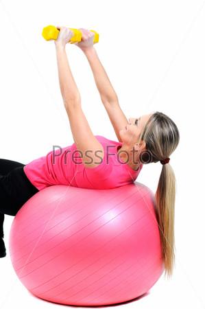 Женщина занимается фитнесом с гантелями
