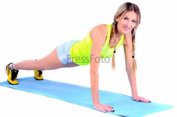 Фотография на тему Красивая молодая женщина делает упражнения для укрепления мышц на полу. Студийный портрет на белом фоне