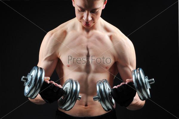 Спортивный парень выполняет упражнения с гантелями на черном фоне