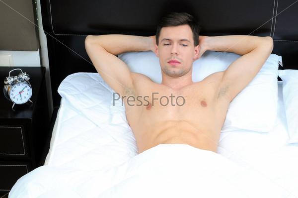 Портрет молодого мужчины на кровати