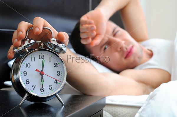 Фотография на тему Мужчина в спальне с будильником на переднем плане