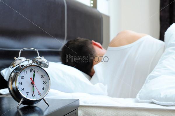Мужчина в спальне с будильником на переднем плане