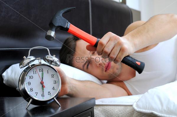 Ленивый мужчина бьет будильник молотком с постели