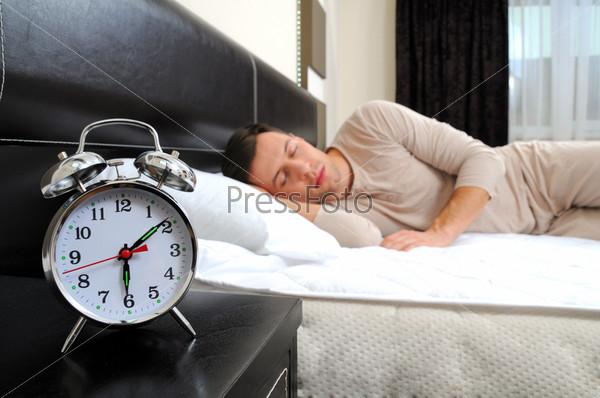 Человек в спальные с будильником на переднем плане