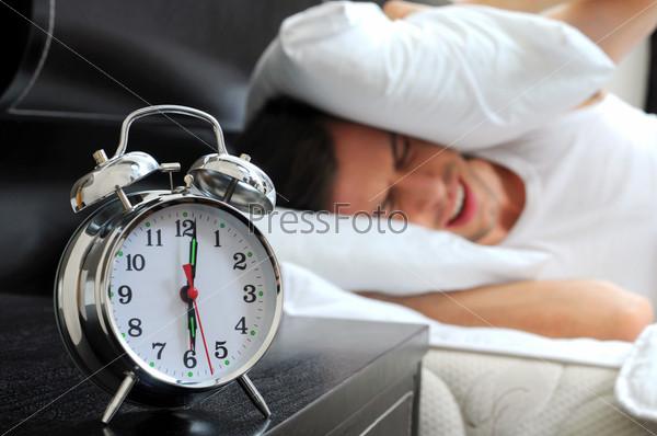 Молодой мужчина закрывает голову подушкой от звонка будильника в спальне