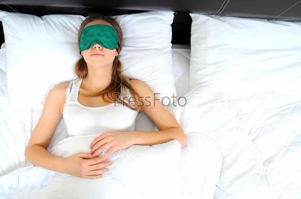 Фотография на тему Молодая красивая женщина спит в постели с маской на глазах