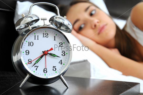 Часы на переднем плане. Женщина не может спать