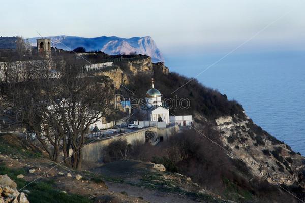 Вид на монастырь, горы и море. Незадолго до заката. Горизонтальное фото