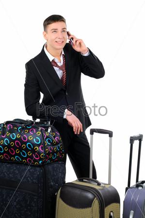 Бизнес-путешественник везет чемодан и говорит по мобильному телефону, изолированный на белом фоне