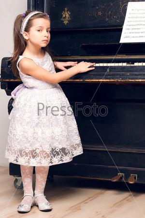 Девочка в красивом платье у фортепиано