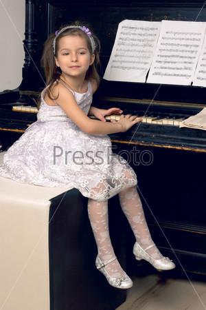Фотография на тему Девочка в красивом платье у фортепиано