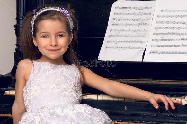 Фотография на тему Девочка в красивом платье сидит за фортепиано