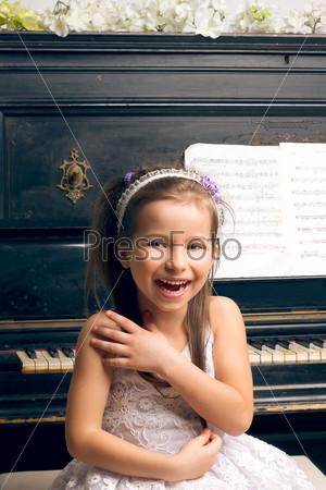 Счастливая девочка в красивом платье сидит за фортепиано