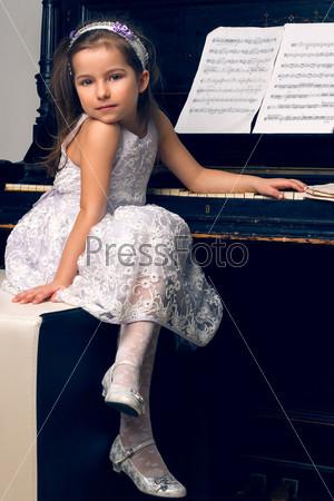 Девочка в красивом платье сидит за фортепиано