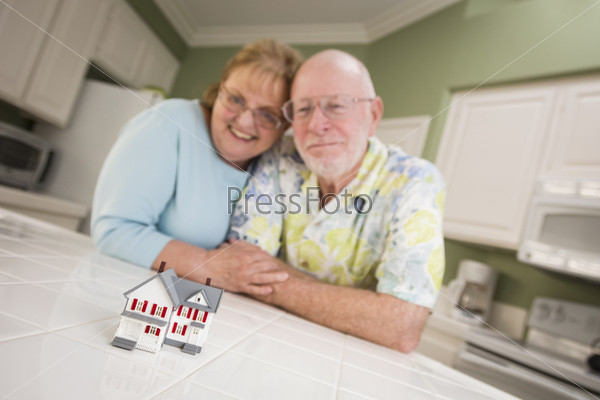Пожилая пара смотрит на маленькую модель дома на столе
