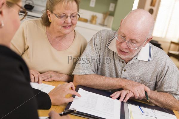 Пожилая пара просматривает документы с агентом в их доме
